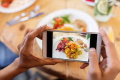 Hands with smartphone picturing food at restaurant. Technology, eating and people concept - hands with smartphone photographing food at restaurant Royalty Free Stock Photo
