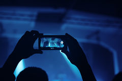 Hands with smartphone recording footage on rock concert royalty free stock photography