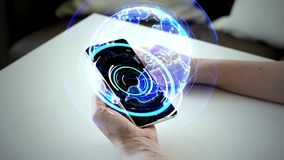 Hands and smartphone with virtual earth hologram. Technology and virtual reality concept - female hands holding smartphone with 3d projection of earth on screen stock footage