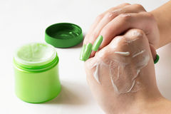 Hands smear the cream on the skin. Female hand  is applied nourishing cream to the skin of green jars of cream Stock Photos