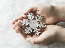 Hands with snowflake. Hands holding shiny snowflake close-up Stock Photography