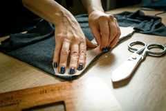 Tailor`s hands cutting out dark green cloth. Hands with soap for drawing a pattern on a cloth Stock Photography