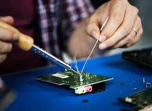 Hands soldering tin on electronics circuit board royalty free stock photos