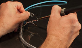 Hands soldering wires together with black background smoke Royalty Free Stock Photography