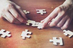 hands solving jigsaw puzzle Royalty Free Stock Images