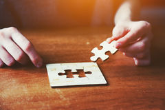 Hands solving jigsaw puzzle Stock Images