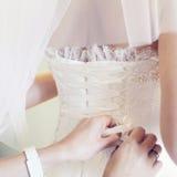 Hands som drar åt en korsett till bruden Royaltyfri Fotografi