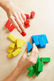 Hands sorting building blocks by color stock images