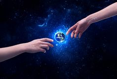 Hands in space touching planet earth. Male god hands about to touch the earth globe in the galaxy with bright shining stars and blue light illustration concept stock photo