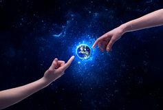 Hands in space touching planet earth. Male god hands about to touch the earth globe in the galaxy with bright shining stars and blue light illustration concept royalty free stock photo
