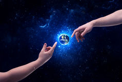 Hands in space touching planet earth. Male god hands about to touch the earth globe in the galaxy with bright shining stars and blue light illustration concept royalty free stock photos