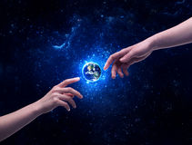 Hands in space touching planet earth. Male god hands about to touch the earth globe in the galaxy with bright shining stars and blue light illustration concept stock images