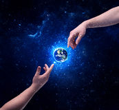 Hands in space touching planet earth. Male god hands about to touch the earth globe in the galaxy with bright shining stars and blue light illustration concept stock photography