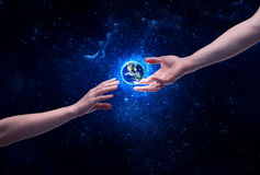 Hands in space touching planet earth. Male god hands about to touch the earth globe in the galaxy with bright shining stars and blue light illustration concept royalty free stock images