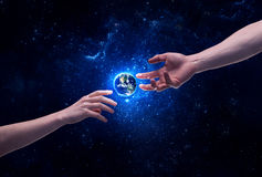 Hands in space touching planet earth. Male god hands about to touch the earth globe in the galaxy with bright shining stars and blue light illustration concept Royalty Free Stock Image