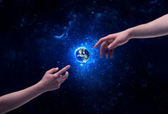 Hands in space touching planet earth. Male god hands about to touch the earth globe in the galaxy with bright shining stars and blue light illustration concept royalty free stock photography