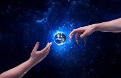 Hands in space touching planet earth. Male god hands about to touch the earth globe in the galaxy with bright shining stars and blue light illustration concept stock photos