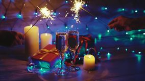 Hands with sparklers on the background of Christmas gifts candles and champagne stock video
