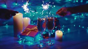 Hands with sparklers, candles, gifts and champagne. The celebration of Christmas stock video footage