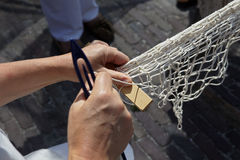 Hands spin a fishing net. Suburb Amsterdam. Museum open-air. Training to craft Royalty Free Stock Images