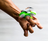 Hands spinner green spin on finger. royalty free stock photography