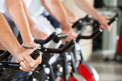 Hands on spinning bikes in fitness Stock Photography