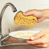 Hands with sponge and dirty dishes over the sink in kitchen Stock Images