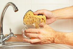 Hands with sponge and dirty glass over the sink in kitchen Royalty Free Stock Photo