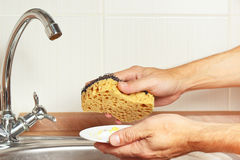 Hands with sponge and dirty saucer over the sink in kitchen Royalty Free Stock Image