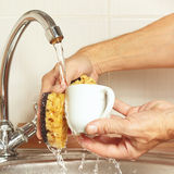 Hands with sponge wash the coffee cup under running water in kitchen Royalty Free Stock Images