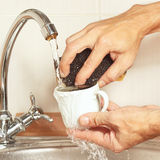 Hands with sponge wash the cup under running water in kitchen Stock Image