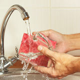 Hands with sponge wash the dirty glass under running water in kitchen Stock Images