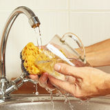 Hands with sponge wash the glass under running water in kitchen Royalty Free Stock Photos