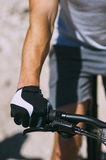 Hands in sports gloves, bicycle and wheel Stock Image