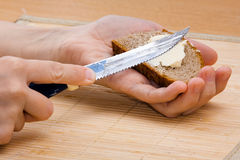 Hands spreading butter on piece of rye bread, closeup Royalty Free Stock Image