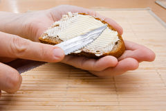Hands spreading butter on piece of rye bread Royalty Free Stock Photos