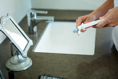 hands squeezing toothpaste onto a toothbrush Royalty Free Stock Photo