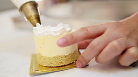 Hands squeezing  whipped cream pastry bag to decorate the cake topping stock video footage
