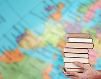 Hands with stacked books. And geographic map royalty free stock photo