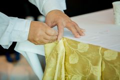 Hands of staff preparing the tablecloth with pin and decorations royalty free stock photo