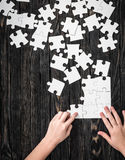 Hands starting to collect puzzle pieces Stock Photography