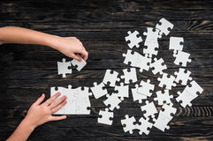 Hands starting to collect puzzle pieces Stock Image