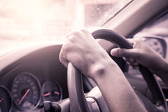 Hands on steering wheel of car driving Stock Photo