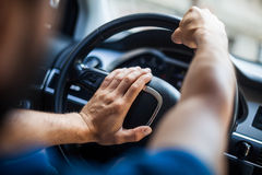 Hands on steering wheel, honking. Close up shot of a man's hands holding a car's steering wheel and honking the horn Stock Images