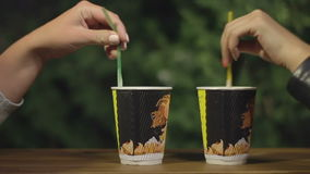 Hands stir cappuccino in a paper cup stock video