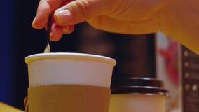 Hands stir sugar in cup of hot drink takeaway. Close up shot. Hands stir sugar in cup of hot drink takeaway stock footage