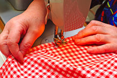 Hands stitching denim cloth Stock Photo