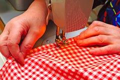 Hands stitching denim cloth Stock Photo