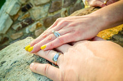 Hands on stone with Wedding Rings Stock Image