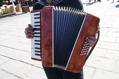 Hands of a street busker accordionist Royalty Free Stock Image